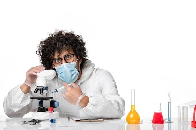 Mężczyzna lekarz w kombinezonie ochronnym i masce do pracy z mikroskopem na białym