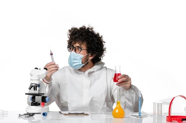Mężczyzna lekarz w kombinezonie ochronnym i masce pracujący z roztworami na białym