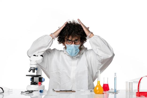 Mężczyzna lekarz w kombinezonie ochronnym i masce siedzącej na białym