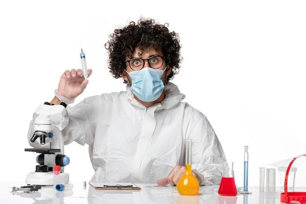 Mężczyzna lekarz w kombinezonie ochronnym i masce trzymającej zastrzyk na białym tle