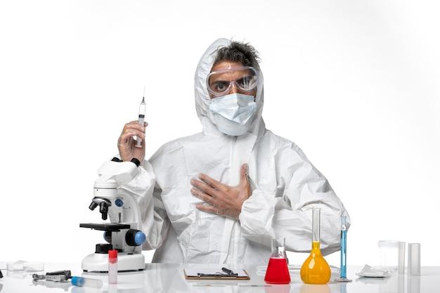 Mężczyzna lekarz w kombinezonie ochronnym i sterylną maską trzymającą zastrzyk na białym tle