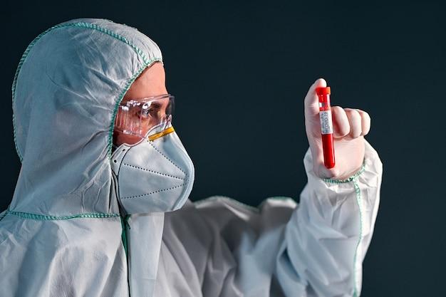 Mężczyzna lekarz w kombinezonie ochronnym, okularach i respiratorze trzyma w rękach probówkę z badaniem krwi na obecność covid 19 pojedynczo na czarno.