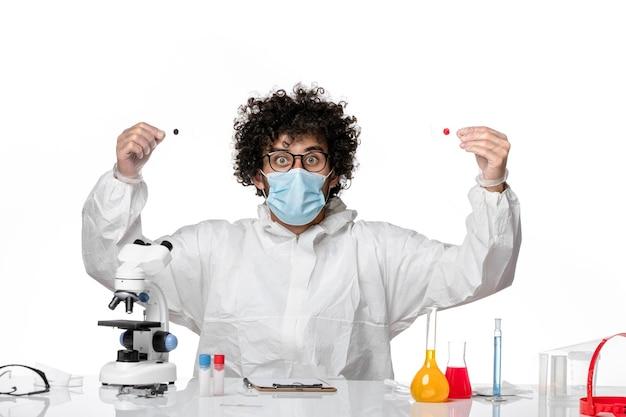 Mężczyzna lekarz w kombinezonie ochronnym sterylna maska siedzi na białym