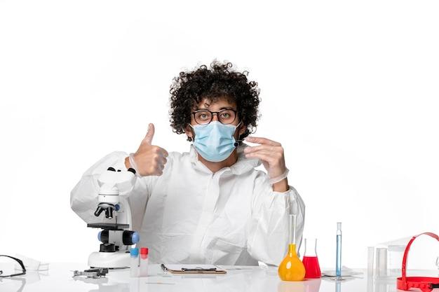 Mężczyzna lekarz w kombinezonie ochronnym sterylna maska trzymająca próbkę na białym