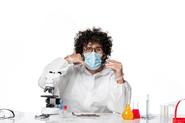 Mężczyzna lekarz w kombinezonie ochronnym sterylna maska trzymająca próbkę na jasnym białym tle