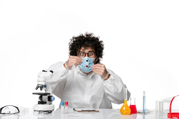 Mężczyzna lekarz w kombinezonie ochronnym sterylna maska trzymająca próbki na białym