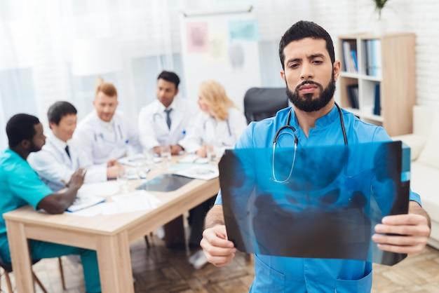 Mężczyzna lekarz w niebieskim płaszczu pokazuje zdjęcie rentgenowskie.