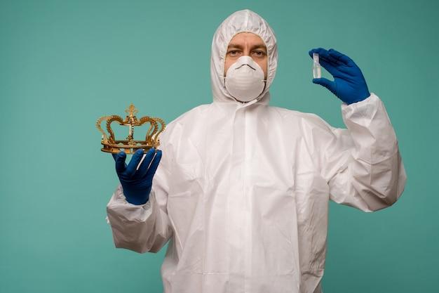 Mężczyzna lekarz w ochronnym kombinezonie i masce trzyma w rękach ampułkę ze szczepionką i koroną
