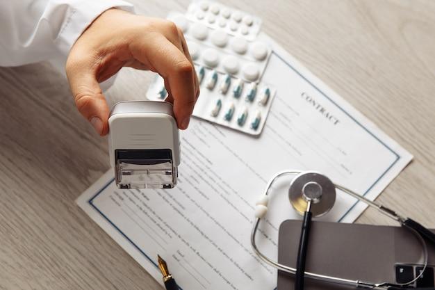 Mężczyzna lekarz w publicznym gabinecie lekarskim z pigułkami i stetoskopem stempluje kontrakt medyczny. koncepcja opieki zdrowotnej i medycyny