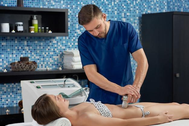 Mężczyzna lekarz w trakcie wykonywania masażu aparatu do klienta