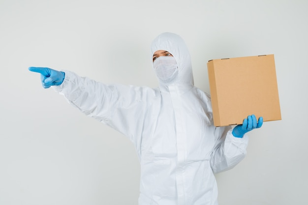 Mężczyzna lekarz wskazując dalej trzymając karton w kombinezonie ochronnym