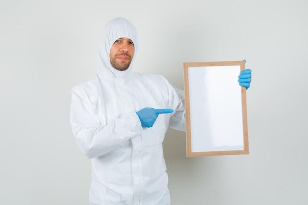 Mężczyzna lekarz wskazując na pustą ramkę w kombinezonie ochronnym
