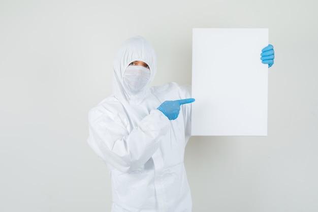 Mężczyzna lekarz, wskazując na puste płótno w kombinezonie ochronnym