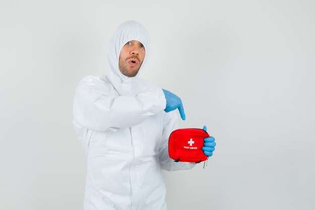 Mężczyzna lekarz wskazując na zestaw pierwszej pomocy w kombinezonie ochronnym, rękawiczkach i patrząc zdziwiony.