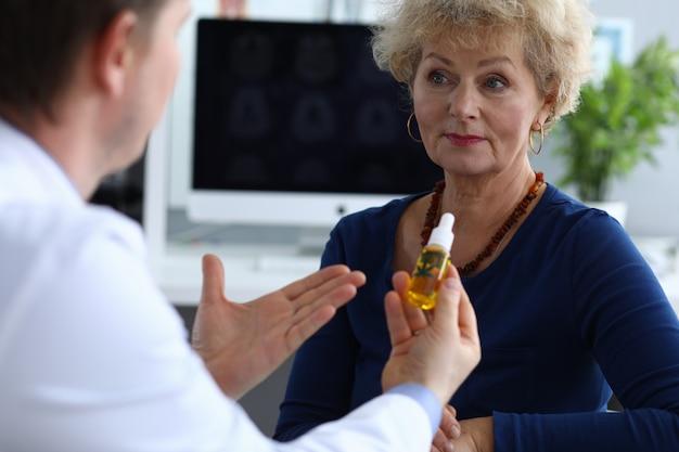 Mężczyzna lekarz wyjaśnia kobiecie zalety oleju konopnego