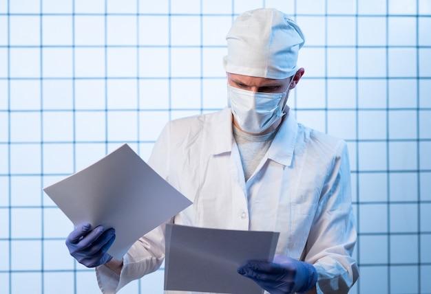 Mężczyzna lekarz z plikami w szpitalu, trzymając schowek i wypisując receptę