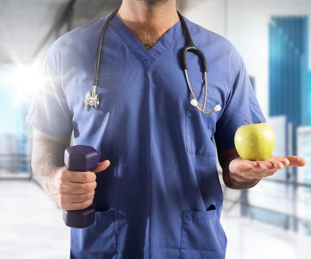 Mężczyzna lekarz z wagi jabłka i hantle