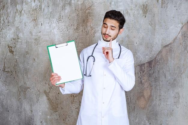Mężczyzna lekarz ze stetoskopem trzyma historię pacjenta i wygląda zamyślony.