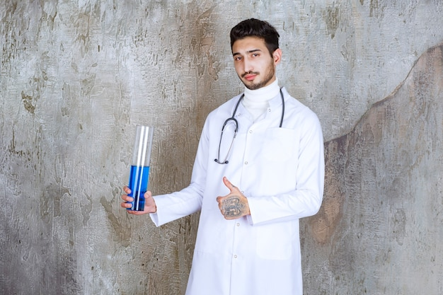Mężczyzna lekarz ze stetoskopem trzyma kolbę chemiczną z niebieskim płynem w środku i pokazuje udany znak dłoni.