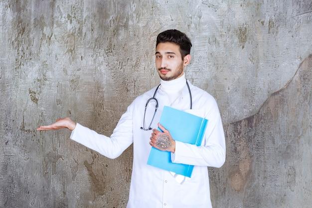 Mężczyzna lekarz ze stetoskopem trzyma niebieski folder i wchodzi w interakcję z osobą w pobliżu
