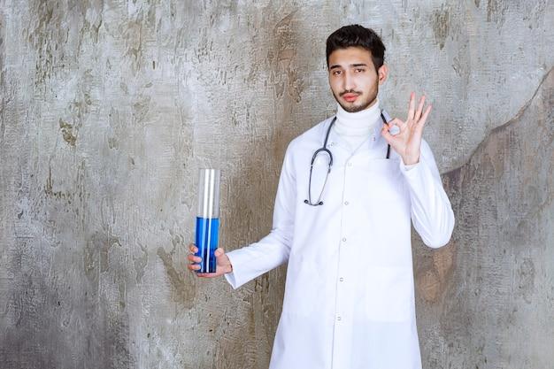 Mężczyzna lekarz ze stetoskopem trzymający butelkę chemiczną z niebieskim płynem w środku i pokazujący udany znak ręką