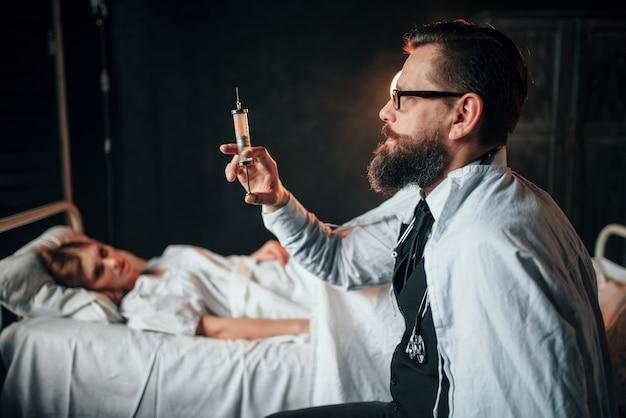 Mężczyzna lekarz ze strzykawką przeciwko chorej kobiecie w łóżku