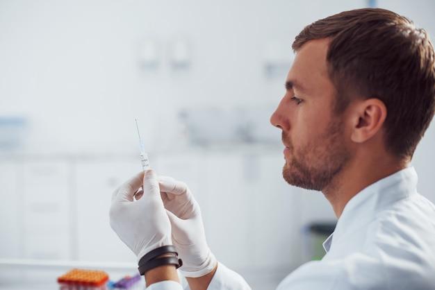 Mężczyzna lekarz ze strzykawką przygotowuje się do pobrania krwi w sali przychodni.