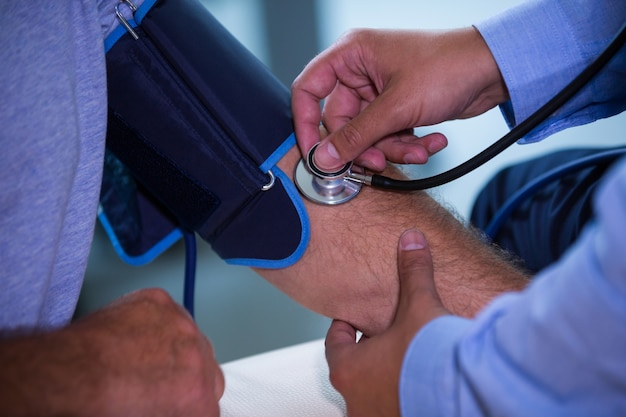 Mężczyzna lekarza kontroli ciśnienia krwi pacjenta
