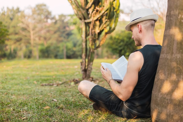 Mężczyzna leżący na drzewie czyta książkę. turysta w kapeluszu czyta książkę w parku. mężczyzna czyta książkę. koncepcja relaksu i na świeżym powietrzu.