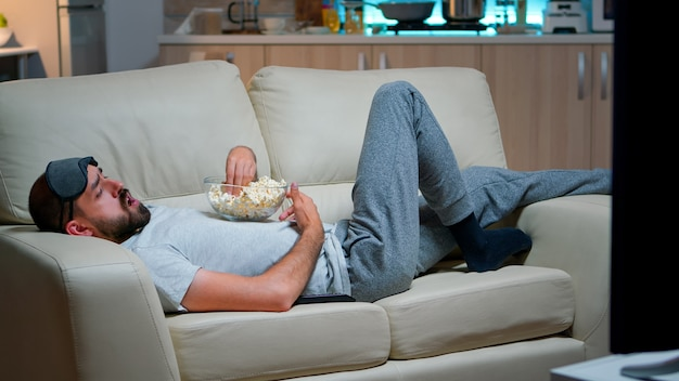 Mężczyzna leżący na kanapie, jedzący popcron i oglądając telewizję