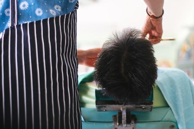 Mężczyzna leżący na kanapie, podczas gdy kompetentny fryzjer w czarnych rękawiczkach goli brodę ostrą brzytwą