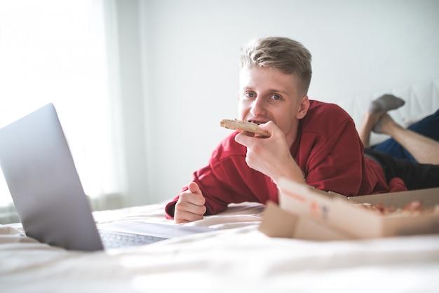Mężczyzna leżący na łóżku z laptopem i pudełkiem po pizzy