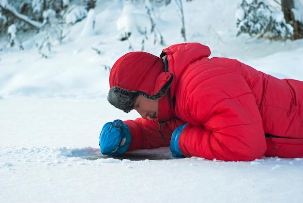 Mężczyzna leży na lodzie zimowej rzeki i patrzy przez lód na oczyszczoną ze śniegu działkę