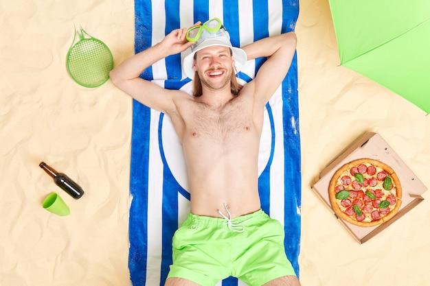 Mężczyzna leży na pasiastym ręczniku cieszy się leniwym letnim dniem na plaży w kapeluszu przeciwsłonecznym maska do snorkelingu je apetyczną pizzę relaksuje się radośnie patrzy na kamerę opala się odpoczywa w tropikalnym kurorcie