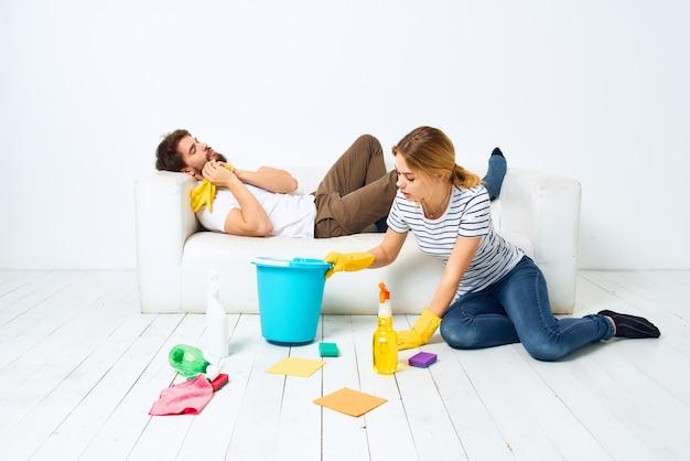 Mężczyzna leży na sofie, kobieta myje podłogi