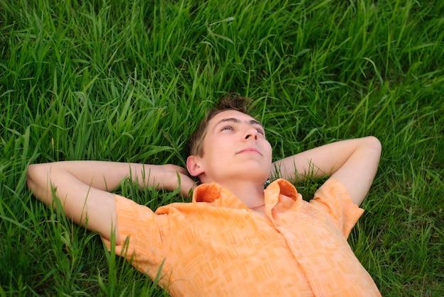 Mężczyzna leży na trawie i patrzy w górę. shallow dof. portret na zewnątrz