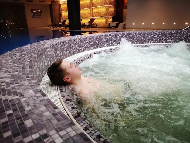 Mężczyzna Leży W Jacuzzi W Hotelu Spa, Relaksując Się W Basenie. Premium Zdjęcia