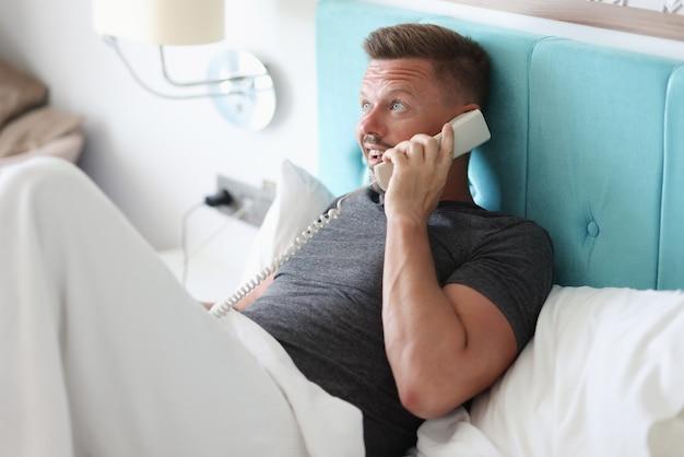 Mężczyzna leży w łóżku w pokoju hotelowym i rozmawia przez telefon.