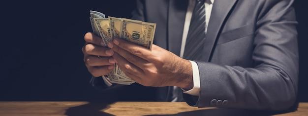 Mężczyzna liczący pieniądze w dolarach amerykańskich w prywatnym pokoju, panoramiczny baner