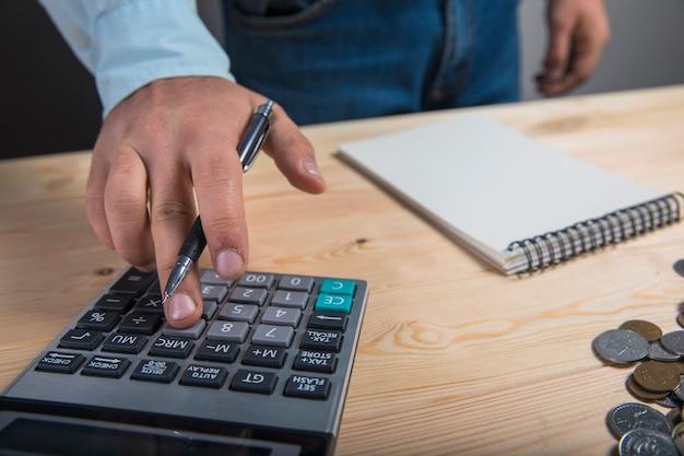 Mężczyzna liczy na kalkulatorze na pulpicie