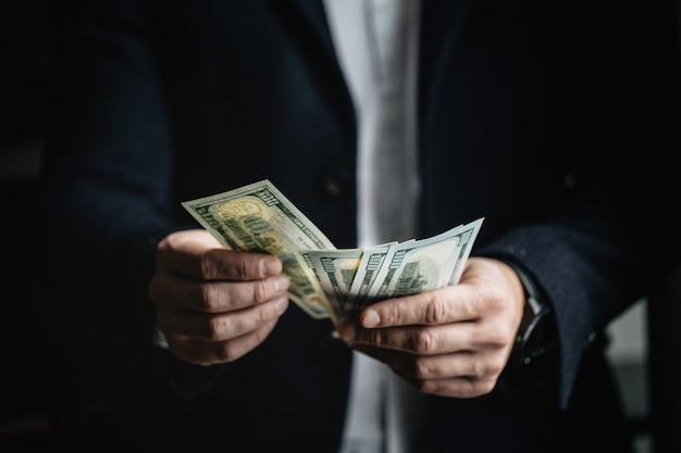 Mężczyzna liczy pieniądze, mężczyzna w biznesie odziewa z dolarami.