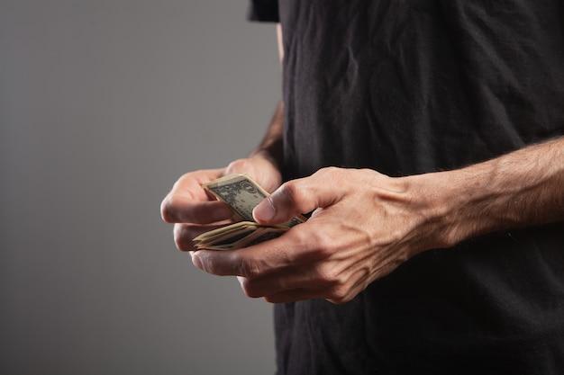 Mężczyzna liczy pieniądze na brązowym tle