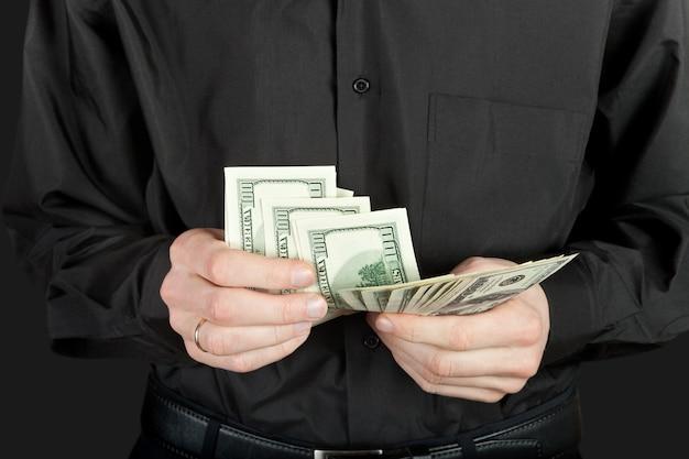 Mężczyzna liczy pieniądze w rękach dolara usa