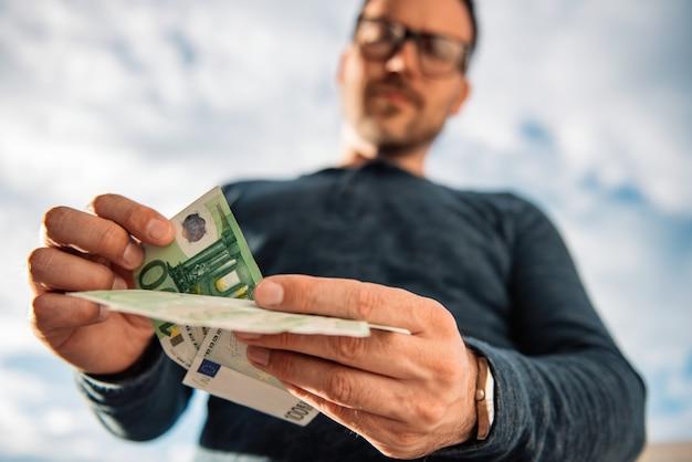 Mężczyzna liczy pieniądze