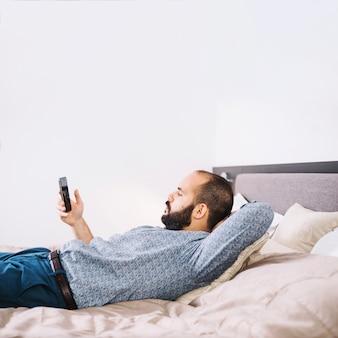 Mężczyzna lounging z smartphone na łóżku