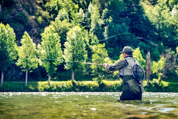 Mężczyzna łowi pstrągi i łososie w rzekach katalońskich pirenejów z całym sprzętem do wędkarstwa sportowego