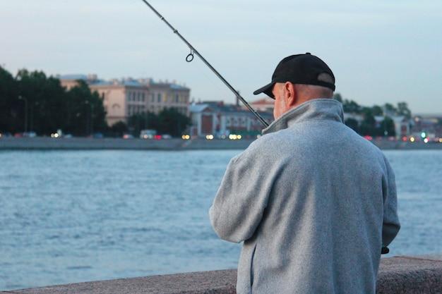 Mężczyzna łowi ryby na miejskiej promenadzie