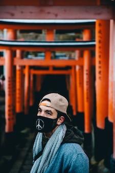 Mężczyzna ma na sobie beżową czapkę, szalik i czarną maskę stojącą na rozmytym tle bramy świątyni