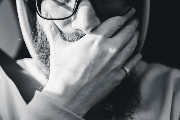 Mężczyzna ma na sobie czarne oprawione okulary
