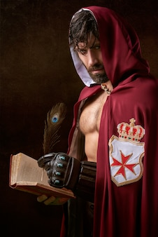 Mężczyzna ma na sobie czerwoną kurtkę z kapturem, trzymając tytułową książkę